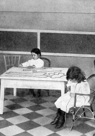 Montessori teaching method - early 20th century. Children counting strings of beads - one of 100 and one of 1000. Educational approach developed by Italian physician and educator Maria Montessori. 1870Â 1952.  (Photo by Culture Club/Getty Images) *** Local Caption ***