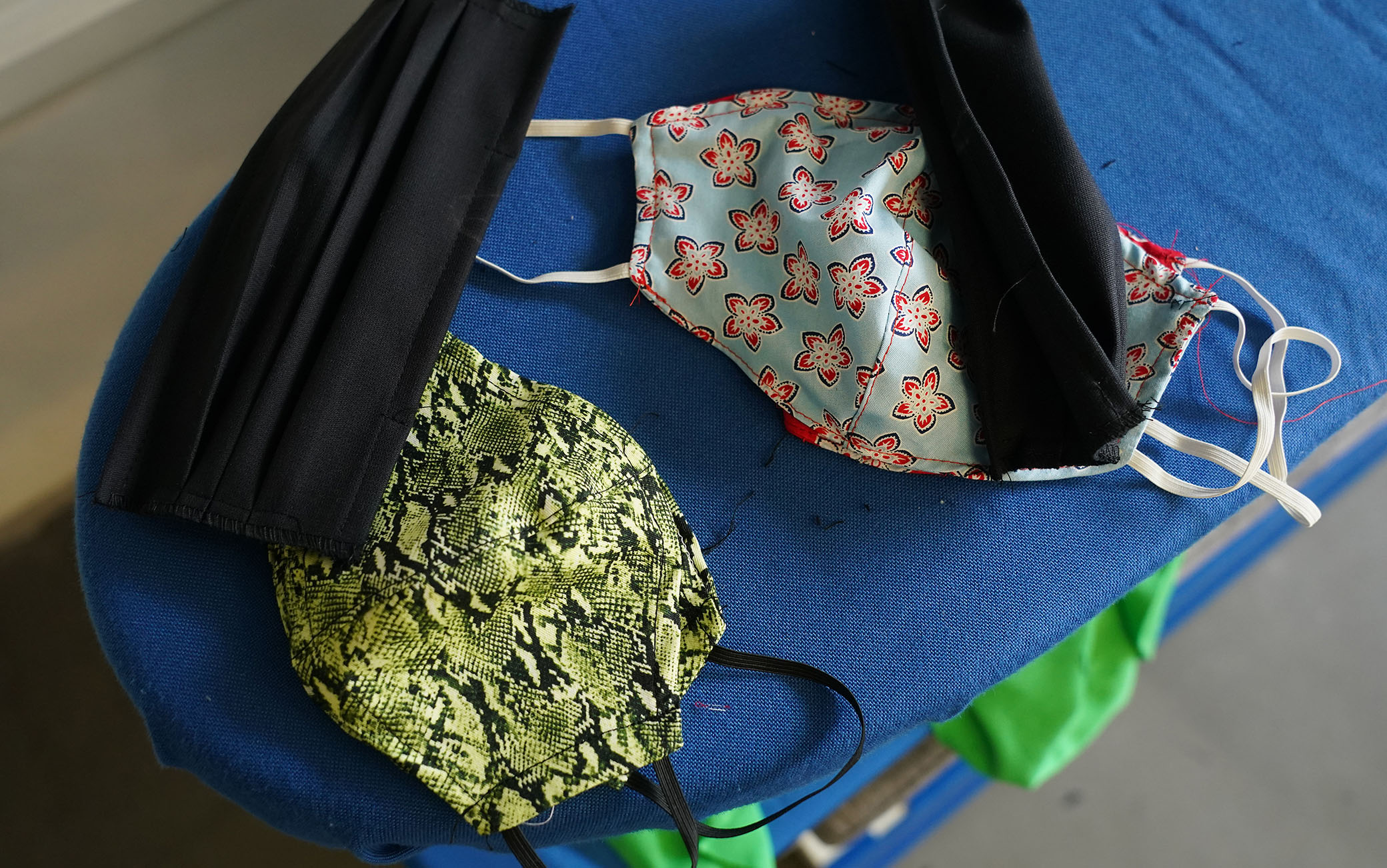 """BERLIN, GERMANY - APRIL 02: Made-to-order protective face masks lie on an ironing board at the workshop of master tailor Ala Hadye on April 02, 2020 in Berlin, Germany. Hadye, who has had to close her shop due to nationwide measures enacted to slow the spread of the coronavirus, says she is making 30 to 40 masks per week on custom order from her customers. """"I could be making masks all week,"""" she said, but says she turns large orders down and concentrates instead on her core customers. """"There are so many others making masks"""", she says of other tailors she knows. Since her shop is closed she sends the masks to her customers by post rather than having them come to the shop. (Photo by Sean Gallup/Getty Images)"""