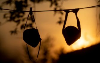 A view shows face masks put up to dry on a clothesline on April 13, 2020 as the sun sets in Rome, during the country's lockdown aimed at curbing the spread of the COVID-19 infection, caused by the novel coronavirus. (Photo by Tiziana FABI / AFP) (Photo by TIZIANA FABI/AFP via Getty Images)