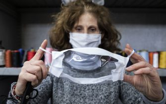 """Loredana Perrone holds a fabric and plastic see-through mask for the hearing and speech impaired, manufactured at her """"Fantasia Tessile"""" factory on April 22, 2020 in Grugliasco, near Turin. - Francesco Tortorelli, owner of auto spare parts dealer """"Grugliasco Ricambi"""", is the creator and investor in the project to product masks for the hearing and speech impaired, in collaboration with Loredana Perrone, owner of the """"Fantasia Tessile"""" textile factory, at risk of closure due to the coronavirus pandemic. (Photo by MARCO BERTORELLO / AFP) (Photo by MARCO BERTORELLO/AFP via Getty Images)"""