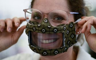 Sandra Bagus, managing director of Bagus hearing aids, presents a selfmade mask for deaf people in her shop in Essen, western Germany on May 12, 2020 amid the ongoing Covid-19, coronavirus pandemic. - The hearing aid acoustician Bagus designed a mouth and nose protector with a viewing window for deaf people. With one of these masks, conversations with hearing-impaired customers who depend on lip-reading are possible. (Photo by Ina FASSBENDER / AFP) (Photo by INA FASSBENDER/AFP via Getty Images)