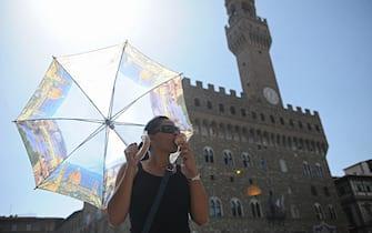 Una donna mangia un gelato e si protegge con un ombrello dal sole a Firenze, 21 giugno 2012. ANSA/MAURIZIO DEGL' INNOCENTI