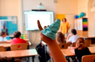 A protective facemask is seen on the hand of a student raising his arm during class at the Carl Orff primary school in west Berlin on August 10, 2020, as school resumed after the summer break in Berlin and several other German states amid a Coronavirus Covid-19 pandemic. (Photo by Tobias SCHWARZ / AFP) (Photo by TOBIAS SCHWARZ/AFP via Getty Images)