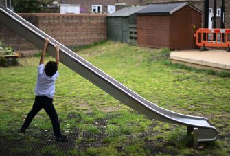 A year two student hangs on a slide during break time at St Luke's Church of England Primary School in East London on September 3, 2020. - Pupils in Britain have on Thursday begun to return to schools for the first time since they were all closed in March, due to the COVID-19 pandemic. (Photo by DANIEL LEAL-OLIVAS / AFP) (Photo by DANIEL LEAL-OLIVAS/AFP via Getty Images)