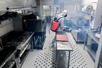 A man disinfects the kitchen of a restaurant in Envigado municipality, near Medellin, Antioquia department, Colombia, on July 1, 2020, amid the COVID-19 pandemic. - Restaurants which were planning to reopen on July 1st are still waiting for the final approval from the government to do so under strict measures to prevent the spread of the new coronavirus. (Photo by JOAQUIN SARMIENTO / AFP) (Photo by JOAQUIN SARMIENTO/AFP via Getty Images)