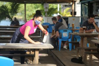 A waitress with a mask disinfects a table of a restaurant by the sea in Mamoudzou on the French Indian Ocean island of Mayotte, on June 4, 2020, as restaurants and bars re-open while measures to curb the spread of the COVID-19 (novel coronavirus) are maintained in Mayotte over concerns about the continued spread of the virus there and a fragile health system. (Photo by Ali AL-DAHER / AFP) (Photo by ALI AL-DAHER/AFP via Getty Images)