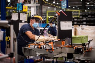 An employee, wearing a protective face mask, assembles a battery-pack for electric cars at the assembly line at the PSA Peugeot Citroen plant in Trnava, Slovakia on July 16, 2020. - French carmaker PSA's Slovak car plant faces an uncertain future because of its declining competitiveness and coronavirus-related losses, senior executives said. PSA Slovakia deputy head told journalists that the plant, which employs 4,500 people and produces Citroën C3 and Peugeot 208 models, was bidding to manufacture another model to stay on its feet. (Photo by VLADIMIR SIMICEK / AFP) (Photo by VLADIMIR SIMICEK/AFP via Getty Images)