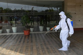 A man wearing Personal Protective Equipment (PPE) sanitizes Ambience mall as places of religious worship, hotels, restaurants and shopping malls are allowed to operate again after more than two months of lockdown imposed as a preventive measure against the COVID-19 coronavirus in New Delhi on June 8, 2020. (Photo by Prakash SINGH / AFP) (Photo by PRAKASH SINGH/AFP via Getty Images)