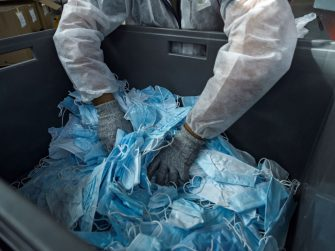 A worker at the start-up Plaxtil company handles protective masks as they are made ready for recycling into plastic to make visors, door openers, mask fasteners, on August 25, 2020 in Chatellerault, western France. - The use of disposable masks has become an environmental issue with people around the world using and throwing away millions of masks worn to curb the spread of the novel coronavirus, COVID-19. (Photo by GUILLAUME SOUVANT / AFP) (Photo by GUILLAUME SOUVANT/AFP via Getty Images)