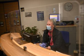 An employee passenger wearing PPE (personal protective equipment), including a face mask as a precautionary measure against COVID-19, sits behind a perspex safety screen at an information desk in Manchester Airport in northern England, on June 8, 2020, as the UK government's planned 14-day quarantine for international arrivals to limit the spread of the novel coronavirus begins. (Photo by Oli SCARFF / AFP) (Photo by OLI SCARFF/AFP via Getty Images)