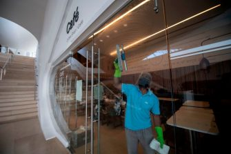 A worker disinfects a window at the coffee shop of the Museum of Tomorrow prior to its reopening in Rio de Janeiro, Brazil on September 4, 2020, amid the COVID-19 novel coronavirus pandemic. - India, the United States and Brazil remain the three countries recording the greatest number of new cases over the past seven days, with 77,596, 40,875 and 40,035 cases respectively per day on average, according to an AFP count on Friday at 1100GMT. (Photo by MAURO PIMENTEL / AFP) (Photo by MAURO PIMENTEL/AFP via Getty Images)
