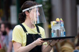 CARDIFF, WALES - AUGUST 12: A woman wearing a plastic face visor serves drinks outdoors at Gin and Juice gin bar on August 12, 2020 in Cardiff, Wales. Coronavirus lockdown measures continue to be eased as the number of excess deaths in Wales falls below the five-year average. (Photo by Matthew Horwood/Getty Images)