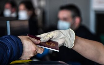 A passenger (L) hands his passport to an employee as he checks in at the counter of China Southern Airlines at Rome's Fiumicino airport for a flight returning to Wuhan, China, after it landed early on January 23, 2020. - China banned trains and planes from leaving a major city at the centre of a virus outbreak on January 23, seeking to seal off its 11 million people to contain the contagious disease that has claimed 17 lives, infected hundreds and spread to other countries. (Photo by Tiziana FABI / AFP) (Photo by TIZIANA FABI/AFP via Getty Images)