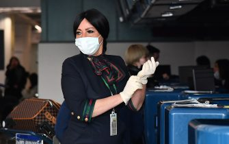 An airport employee puts on protective gloves and respiratory mask as she prepares to do passengers' check in at the counter of China Southern Airlines at Rome's Fiumicino airport, for a flight returning to Wuhan, China, after it landed early on January 23, 2020. - China banned trains and planes from leaving a major city at the centre of a virus outbreak on January 23, seeking to seal off its 11 million people to contain the contagious disease that has claimed 17 lives, infected hundreds and spread to other countries. (Photo by Tiziana FABI / AFP) (Photo by TIZIANA FABI/AFP via Getty Images)