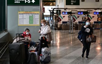 Passengers wearing a respiratory mask wait in a terminal at Milan-Malpensa airport in Ferno, northwest of Milan, in one of Italy's quarantine red zones on March 9, 2020. - Millions of people in northern Italy were in lockdown as officials struggled to contain the spread of the deadly coronavirus COVID-19. (Photo by MIGUEL MEDINA / AFP) (Photo by MIGUEL MEDINA/AFP via Getty Images)