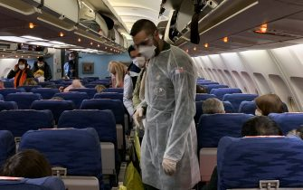 TOPSHOT - French citizens arrive and settle aboard of an evacuation plane with destination southeastern France, before departure from Wuhan Airport (WUH), China, on the night between January 30, 2020 and January 31, 2020, as they are repatriated from the coronavirus hot zone. - The nearly 200 passengers repatriated are expected to arrive in France on January 31, 2020 and will be placed in quarantine for 14 days in a holiday center in Carry-le-Rouet, near Marseille, southern France. Some 7,700 cases have been confirmed in China, its country of origin, with at least 170 fatalities. The virus has spread from the city of Wuhan across China to more than 15 countries, with about 60 cases in Asia, Europe, North America and, most recently, the Middle East. (Photo by Hector RETAMAL / AFP) (Photo by HECTOR RETAMAL/AFP via Getty Images)