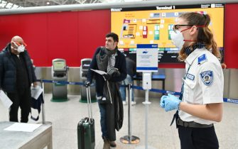 An airport security staff, wearing a respiratory mask (R), controls passengers at Rome's Fiumicino international airport March 13, 2020. - Rome's Ciampino airport will shut to passenger flights from March 13, authorities said, with a terminal also closing at the city's main Fiumicino facility next week as airlines slash flights to Italy over the coronavirus outbreak. (Photo by Andreas SOLARO / AFP) (Photo by ANDREAS SOLARO/AFP via Getty Images)
