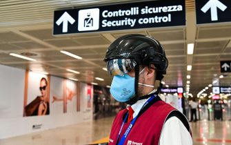 """A Fiumicino airport employee wearing a """"Smart-Helmet"""" portable thermoscanner to screen passengers and staff for COVID-19, stands prepared at boarding gates on May 5, 2020 at Rome's Fiumicino airport during the country's lockdown aimed at curbing the spread of the COVID-19 infection, caused by the novel coronavirus. (Photo by ANDREAS SOLARO / AFP) (Photo by ANDREAS SOLARO/AFP via Getty Images)"""