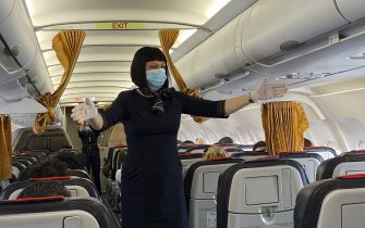 MILAN, ITALY - JUNE 03:  Flight hostess wearing PPE gives directions to passengers on the plane on the first day of reopening of Malpensa Airport after the lockdown on June 03, 2020 in Milan, Italy. Flights have started again from the ease of the Covid-19 lockdown on June 3rd.  (Photo by Lorenzo Palizzolo/Getty Images)