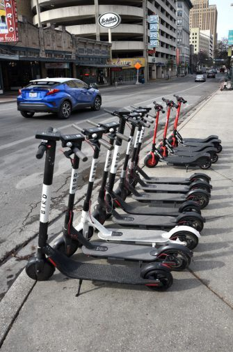 SAN ANTONIO, TEXAS - DECEMBER 11, 2018:  A row of electric rental scooters at a street corner in downtown San Antonio, Texas. (Photo by Robert Alexander/Getty Images)