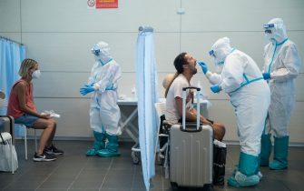 CASELLE TORINESE, ITALY - AUGUST 26: General view of medical staff in full PPE conduct a swab test on travellers after their flight from Ibiza, Spain to Turin on August 26, 2020 in Turin, Italy. At Italian airports, all travelers from countries at risk of Covid-19 are tested with swabs to prevent the spread of Covid 19 in Italy. (Photo by Stefano Guidi/Getty Images)