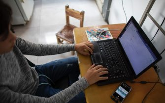 CARACAS, VENEZUELA - APRIL 27: A teenager student Jose Lara studies his daily schoolwork on his laptop at his home in the slum of Catia during the second month of quarantine in the Country on April 27, 2020 in Caracas, Venezuela. Due to the government-ordered coronavirus lockdown, students in Venezuela will have to attend classes remotely until the end of the school year on July 10th. In most cases, teachers connect with their students daily or weekly through e-mail or social media. Online education is a challenge in a country with a very unstable and slow internet service, frequent power outages and low-income households where parents lack of time to spend teaching their kids. (Photo by Leonardo Fernandez Viloria/Getty Images)