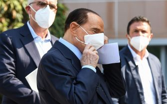Former Italian prime minister Silvio Berlusconi (C) takes off his face mask as he prepares to address the media, as he leaves the San Raffaele Hospital in Milan on September 14, 2020 after he tested posititive for coronavirus and was hospitalized since September 3. (Photo by Piero CRUCIATTI / AFP) (Photo by PIERO CRUCIATTI/AFP via Getty Images)