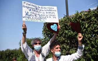 "Supporters of former Italian prime minister Silvio Berlusconi hold a placard reading ""Finally discharged, we thank God for the blessing, a round of applause to the doctors"" as Berlusconi leaves the San Raffaele Hospital in Milan on September 14, 2020 after he tested posititive for coronavirus and was hospitalized since September 3. (Photo by Piero CRUCIATTI / AFP) (Photo by PIERO CRUCIATTI/AFP via Getty Images)"