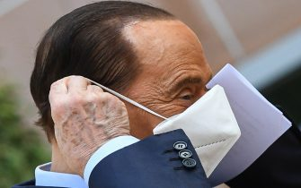 Former Italian prime minister Silvio Berlusconi takes off his mask as he prepares to address the media, as he leaves the San Raffaele Hospital in Milan on September 14, 2020 after he tested posititive for coronavirus and was hospitalized since September 3. (Photo by Piero CRUCIATTI / AFP) (Photo by PIERO CRUCIATTI/AFP via Getty Images)