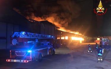 Il vasto incendio divampato stamani nel porto di Ancona. ANSA