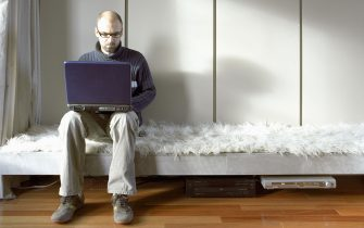 Man on Laptop in Lounge Room. (Photo by Brenda Liu/Construction Photography/Avalon/Getty Images)