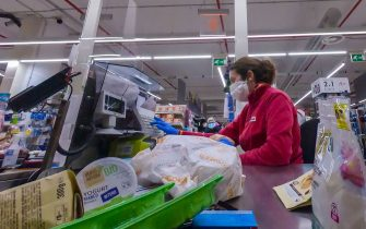 A cashier wearing a face masks processes a customer's payment at a supermarket on March 26, 2020 in the Portuense district of Rome during the country's lockdown following the COVID-19 new coronavirus pandemic. (Photo by ANDREAS SOLARO / AFP) (Photo by ANDREAS SOLARO/AFP via Getty Images)
