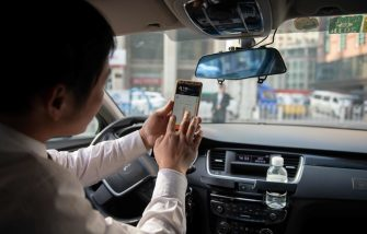 In this picture taken on October 18, 2018, a driver working for ride-sharing company Didi uses his smartphone to choose the best driving route to bring a customer to his destination in Beijing. - Didi is a popular taxi and ride-sharing service in China that is operated via a smartphone app. (Photo by Nicolas ASFOURI / AFP)        (Photo credit should read NICOLAS ASFOURI/AFP via Getty Images)