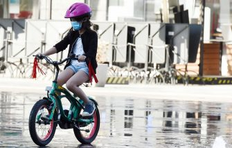 MILAN, ITALY - MAY 04:  A girl with a face mask rides a bicycle at Gae Aulenti square on May 04, 2020 in Milan, Italy. Italy was the first country to impose a nationwide lockdown to stem the transmission of the Coronavirus (Covid-19), and its restaurants, theaters and many other businesses remain closed. (Photo by Stefania D'Alessandro/Getty Images)