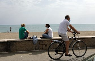 ROME, ITALY - MAY 18: People wearing face masks sit and cycle at the Ostia beach as some restrictions begin to lift during the coronavirus pandemic on May 18, 2020 in Rome, Italy. Today is the first day people are allowed to go to the beaches in the Municipality of Rome after more than two months of a nationwide lockdown meant to curb the spread of Covid-19. (Photo by Elisabetta A. Villa/Getty Images)