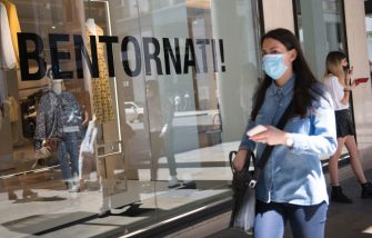 """TURIN, ITALY - MAY 20: Woman with protective mask walks near a shop window with the written """"Welcome back"""" in the city center of Turin on May 20, 2020 in Turin, Italy. Restaurants, bars, cafes, hairdressers and other shops have reopened, subject to social distancing measures, after more than two months of a nationwide lockdown meant to curb the spread of Covid-19. (Photo by Stefano Guidi/Getty Images)"""