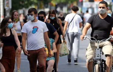 """Cyclists and predestrians wear protective facemasks as they travel on a street in Antwerp on August 6, 2020, as authorities impose additional measures to attempt to curb the spread of the COVID-19 caused by the novel coronavirus"""". - The country with the highest number of deaths attributed to coronavirus compared to its population is Belgium with 85 fatalities per 100,000 inhabitants, followed by the UK at 68, Peru 61, Spain 61, and Italy 58. (Photo by François WALSCHAERTS / AFP) (Photo by FRANCOIS WALSCHAERTS/AFP via Getty Images)"""