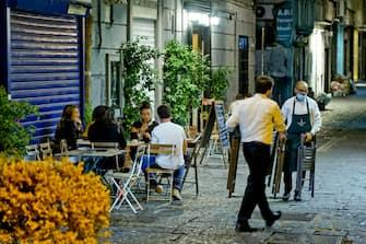 Nella zona dei 'baretti' a Napoli allo scoccare delle 23, come previsto dall'ordinanza anti Covid  del governatore della Campania Vincenzo De Luca -  camerieri e baristi si apprestano a ritirare sedie e tavolini per chiudere i locali sotto gli occhi degli ultimi clienti ottobre  2020 ANSA / CIRO FUSCO