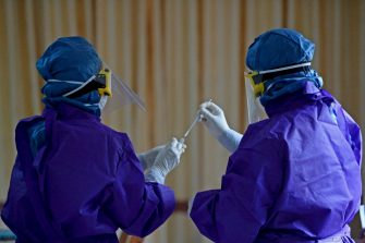 Medical workers wearing Personal Protective Equipment (PPE) gear collect a swab sample from a woman (not pictured) to test for the COVID-19 coronavirus, in Colombo on July 14, 2020. - The country has reported just 2,617 cases with 11 deaths, but army chief Shavendra Silva said nearly half the 1,100 residents and staff at a drug rehab facility near the capital had tested positive in the past week, and some visitors may also have been infected. (Photo by LAKRUWAN WANNIARACHCHI / AFP) (Photo by LAKRUWAN WANNIARACHCHI/AFP via Getty Images)