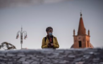 ROME, ITALY - OCTOBER 07: A woman wearing protective mask is reflected in a puddle as she walks at Piazza del Popolo amid Covid-19 pandemic, on October 07, 2020 in Rome, Italy. Today Italian Prime Minister Giuseppe Conte set an order to make the wearing of face masks in outdoor spaces mandatory due to the increase of Covid-19 cases in Italy. Today there has been an increase in new COVID cases in Italy with the number rising to 3678 for the first time in months. (Photo by Antonio Masiello/Getty Images)