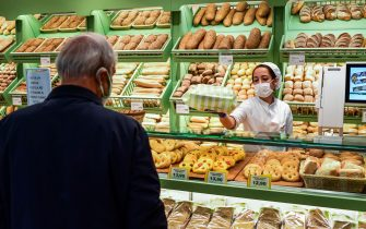 A customer purchases bread at an Esselunga supermarket in Milan's Famagosta district on April 30, 2020, during the country's lockdown aimed at curbing the spread of the COVID-19 infection, caused by the novel coronavirus. (Photo by Miguel MEDINA / AFP) (Photo by MIGUEL MEDINA/AFP via Getty Images)
