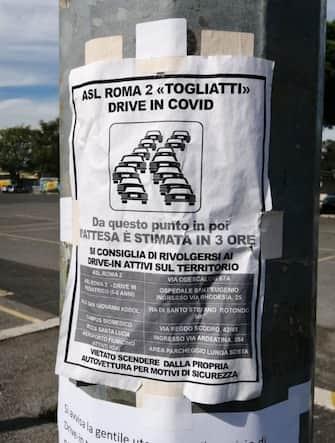 Un cartello attaccato ad un palo della strada sulla Palmiro Togliatti annuncia le lunghe code per accedere al Drive-in ed effettuare il tampone per il Coronavirus, Roma, 6 ottobre 2020. L'attesa è di 4-5 ore. ANSA
