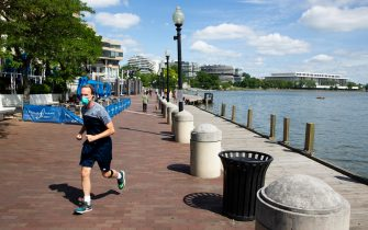 epa08446074 A runner wears a face mask while jogging at the waterfront in Georgetown, Washington, DC, USA, 26 May 2020. The nation's capital may begin lifting coronavirus COVID-19 restrictions as early as 29 May, according to Mayor of Washington, DC, Muriel Bowser. Bowser is expected to make an announcement on 27 May regarding reopening, which could occur if the current data trend continues.  EPA/MICHAEL REYNOLDS