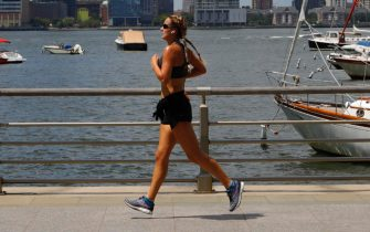 epa08571272 A woman is seen jogging along Battery Park a in New York City, USA, 28 July 2020. Temperatures are forecasted to reach 91 degrees Fahrenheit (33 degrees Celsius) in New York City on 28 July.  EPA/JASON SZENES