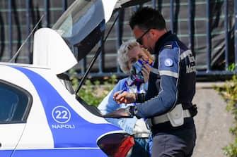 Un agente della Polizia Municipale controlla una persona in strada nonostante le restrizioni  diramate per arginare il pericolo da contagio da Coronavirus, 20 marzo  2020 ANSA / CIRO FUSCO