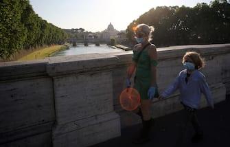 Roma, Italy 6 maggio 2020: Una madre ed il figlio con la mascherina passeggiano per Roma  con lo sfondo di Piazza San Pietro,  durante la fase 2 dell'emergenza Covid-19, dopo due mesi di quarantena nella città di Roma. (MARCO IACOBUCCI / IPA/Fotogramma,  - 2020-05-06) p.s. la foto e' utilizzabile nel rispetto del contesto in cui e' stata scattata, e senza intento diffamatorio del decoro delle persone rappresentate