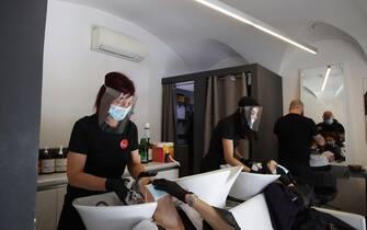 Parrucchiere con i suoi primi clienti nel giorno della riaperture previste nella fase 2 del coronavirus, Brescia 18 maggio 2020. Ansa/Filippo Venezia