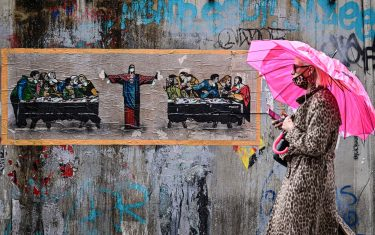 "A woman wearing a protective mask walks past a new mural by Italian street artist TvBoy, entitled ""Supper for six"", inspired by ""The last supper"" by Italian artist Leonardo da Vinci on October 27, 2020 in Naviglio neighbourhood, southern Milan. (Photo by MIGUEL MEDINA / AFP) / RESTRICTED TO EDITORIAL USE - MANDATORY MENTION OF THE ARTIST UPON PUBLICATION - TO ILLUSTRATE THE EVENT AS SPECIFIED IN THE CAPTION (Photo by MIGUEL MEDINA/AFP via Getty Images)"