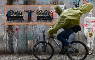 "A man rides his bike in front of a new mural by Italian street artist TvBoy, entitled ""Supper for six"", inspired by ""The last supper"" by Italian artist Leonardo da Vinci on October 27, 2020 in Naviglio neighbourhood, southern Milan. (Photo by MIGUEL MEDINA / AFP) / RESTRICTED TO EDITORIAL USE - MANDATORY MENTION OF THE ARTIST UPON PUBLICATION - TO ILLUSTRATE THE EVENT AS SPECIFIED IN THE CAPTION (Photo by MIGUEL MEDINA/AFP via Getty Images)"