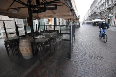 A man with his face covered by a medical mask passes by bicycle next to the tables and stacked chairs of the outdoor area of a bar in the central pedestrian street of Via Dante closed in compliance with anti-covid measures in the Brera district, Milan, Italy 16 November 2020. ANSA/DANIEL DAL ZENNARO